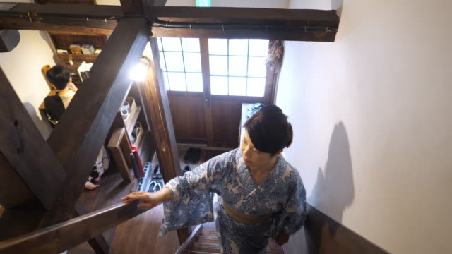 japanese woman in yukata walking up stairs in old japanese 'ryokan' hotel - steps and staircases stock videos & royalty-free footage