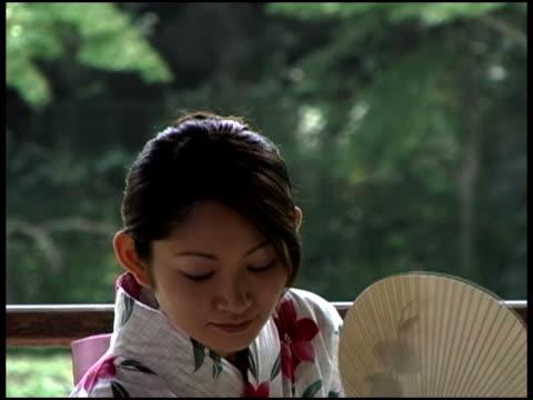 Japanese Woman In YukataFaning Herself On Terrace By Forest Close Up,Fukuoka, JapanJapanese woman in kimono