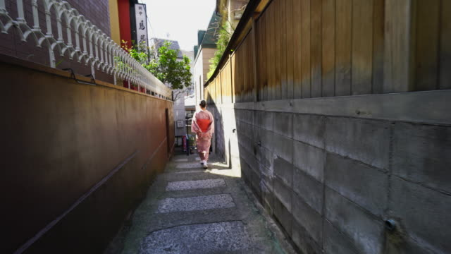 A Japanese woman is going through the narrow stone stair alley, who is wearing kimono at Kagurazaka Tokyo.There is a Ryotei Restaurant Maeda at the corner of the alleyway, and some other restaurants and bars at both side of alley.