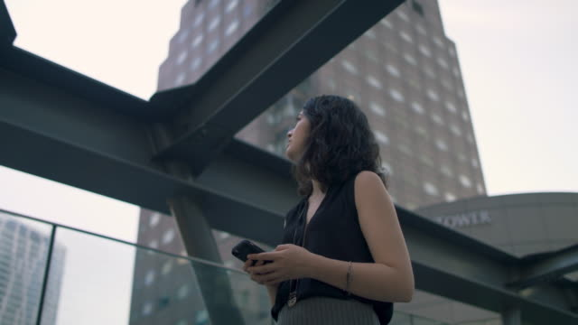 japanese woman looking at phone in tokyo, japan - contemplation stock-videos und b-roll-filmmaterial