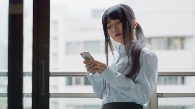 a japanese woman looks at her phone and thinks / tokyo, japan - bronek kaminski stock videos & royalty-free footage