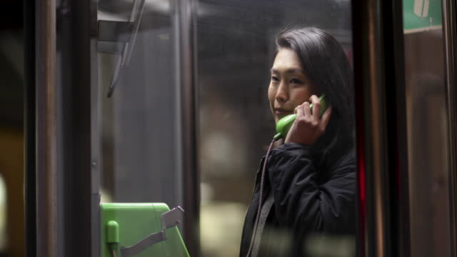 japanese woman making phone call at night. tokyo, japan - 電話ボックス点の映像素材/bロール