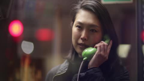 japanese woman making phone call at night. tokyo, japan - telefonzelle stock-videos und b-roll-filmmaterial