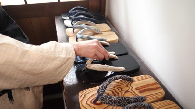 vídeos de stock e filmes b-roll de japanese woman picking up japanese zori geta sandal in old japanese ryokan hotel - sandália