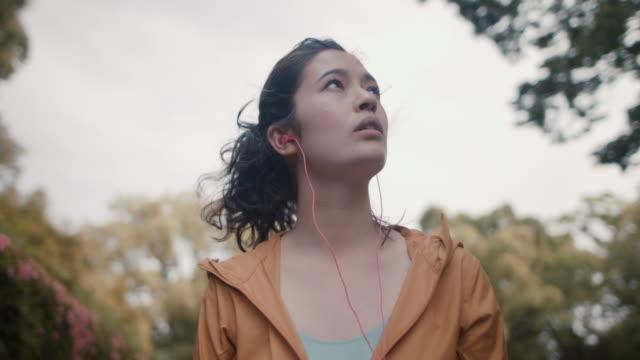 japanese woman putting in headphones and walking among trees in tokyo, japan. - 見上げる点の映像素材/bロール