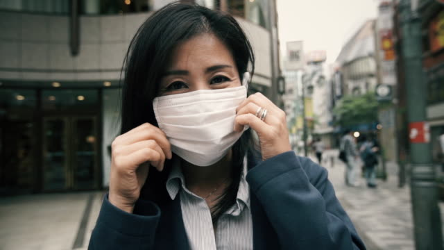 vídeos de stock, filmes e b-roll de japanese woman putting on surgical mask - máscara cirúrgica