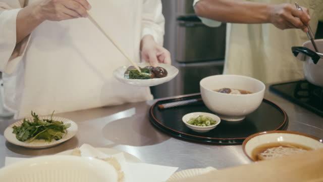 japanese woman putting shiitake mushrooms on soba noodles - shiitake stock videos & royalty-free footage