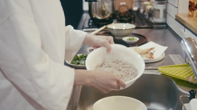 japanese woman rinsing buckwheat soba noodles in the sieve - shiitake stock videos & royalty-free footage