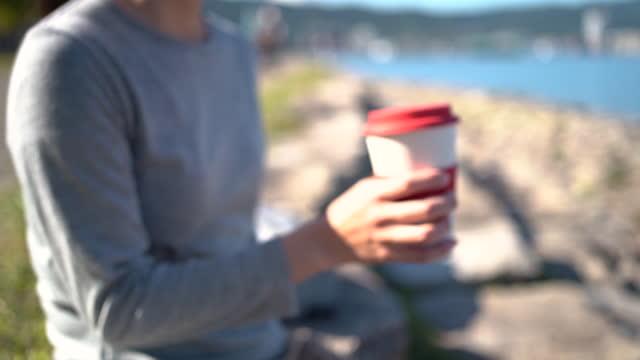 eine japanerin sitzt auf einer steintreppe und trinkt kaffee aus einer wiederverwendbaren kaffeetasse. - cup stock-videos und b-roll-filmmaterial
