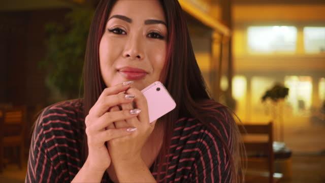 Japanese woman sitting at a restaurant looking at camera