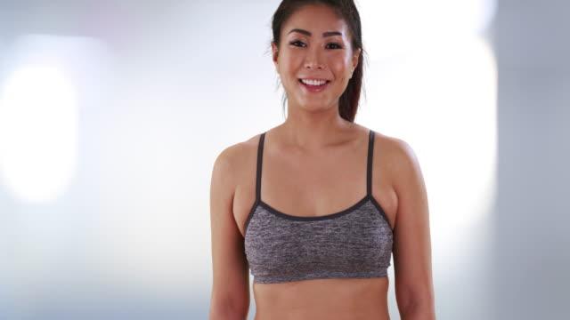 stockvideo's en b-roll-footage met japanese woman standing at the gym smiling - menselijke arm