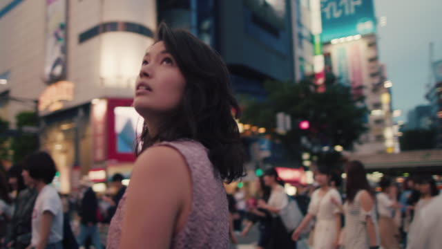 japanese woman standing in the middle of busy intersection looking up / tokyo, japan - erwartung stock-videos und b-roll-filmmaterial