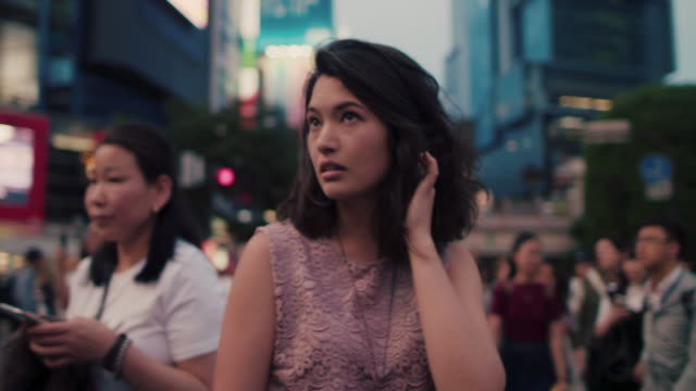vidéos et rushes de japanese woman standing in the middle of busy intersection looking up / tokyo, japan - activité