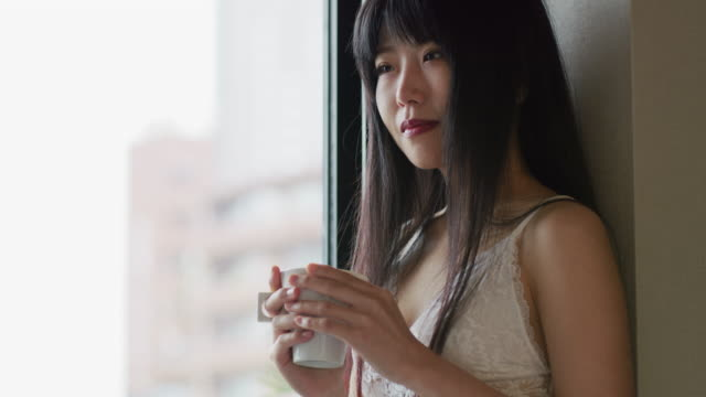 a japanese woman stands contemplating / tokyo, japan - 満たす点の映像素材/bロール
