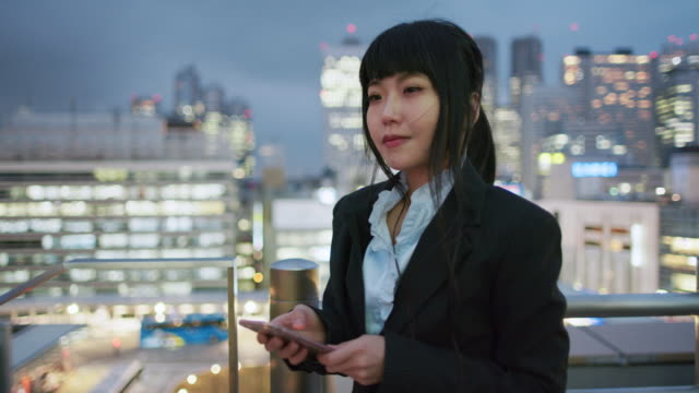 a japanese woman stands thinking and using her phone / tokyo, japan - bronek kaminski stock videos & royalty-free footage