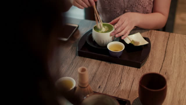 japanese woman stirring matcha tea at a restaurant in tokyo, japan - hausdekor stock-videos und b-roll-filmmaterial