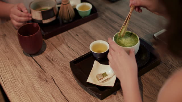 Japanese woman stirring Matcha tea at a restaurant in Tokyo, Japan