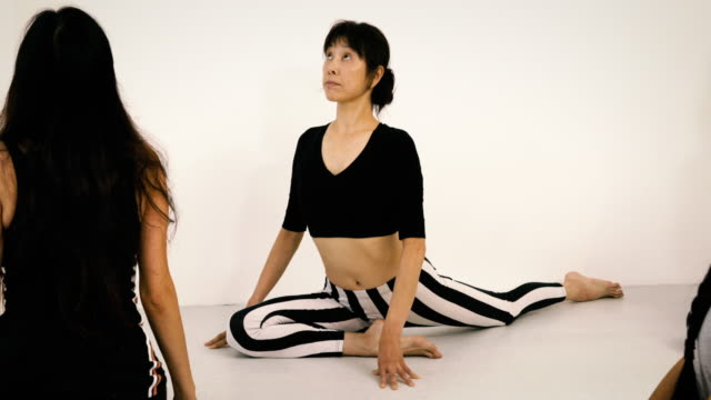 Japanese woman stretching during yoga class