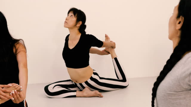 japanese woman stretching during yoga class - solo giapponesi video stock e b–roll