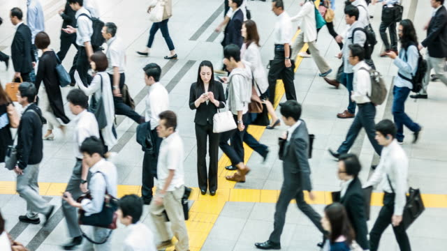 japanese woman talking on the mobile phone surrounded by commuters - standing out from the crowd stock videos & royalty-free footage