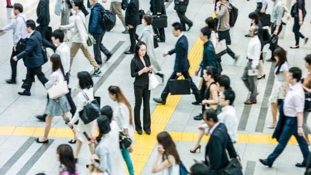 japanese woman talking on the mobile phone surrounded by commuters - japanese culture stock videos & royalty-free footage