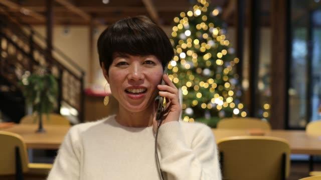 カフェで電話で話す日本人女性 - 中年点の映像素材/bロール