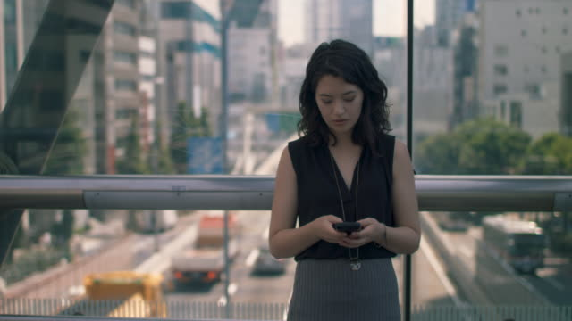 japanese woman typing on phone on footbridge in tokyo, japan - 寄りかかる点の映像素材/bロール