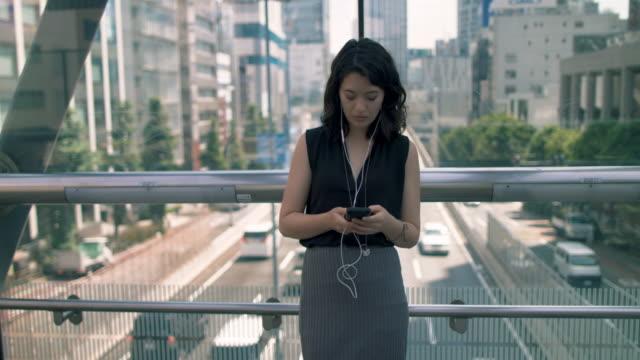 japanese woman typing on phone on footbridge in tokyo, japan - text messaging stock videos & royalty-free footage