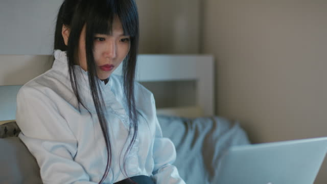 a japanese woman uses a laptop on a bed / tokyo, japan - bronek kaminski stock videos & royalty-free footage