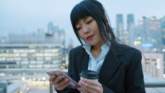a japanese woman uses her phone / tokyo, japan - bronek kaminski stock videos & royalty-free footage