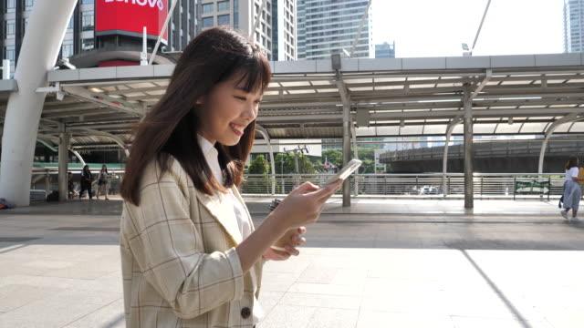 japanische frau mit handy auf straßen in der stadt nach der arbeit - east asian ethnicity stock-videos und b-roll-filmmaterial