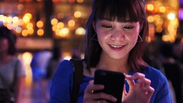夜の街の通りに携帯電話を使用して日本の女性