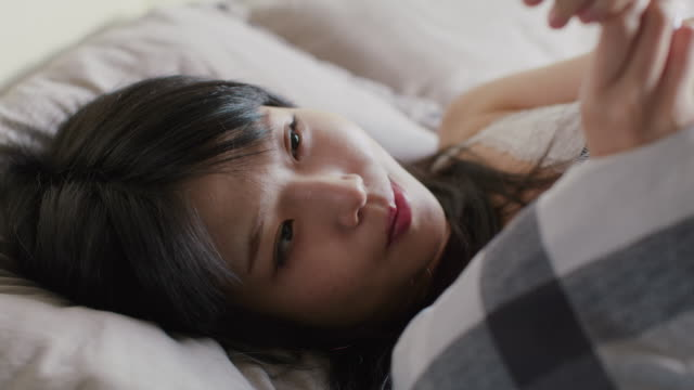 a japanese woman wakes up and checks her phone - bronek kaminski stock videos & royalty-free footage