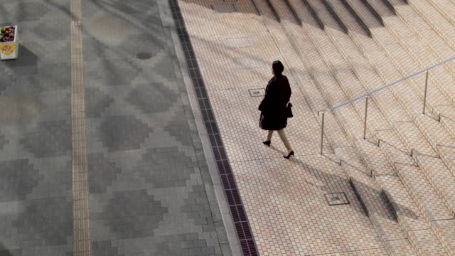 japanese woman walking down steps in business district tokyo, japan - viewpoint点の映像素材/bロール