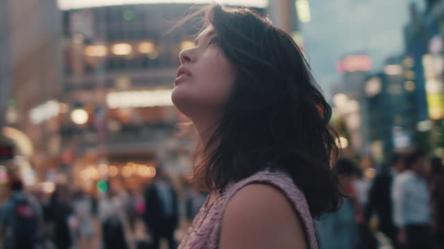 japanese woman walking on busy intersection, looking up / tokyo, japan - 胸を打つ点の映像素材/bロール