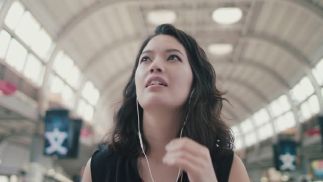 japanese woman walking, talking into headphones microphone in train station in tokyo, japan - looking around stock videos & royalty-free footage
