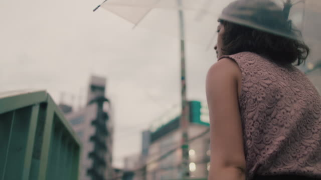 japanese woman walking up stairs with transparent umbrella / tokyo, japan - scale video stock e b–roll