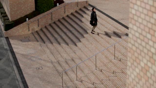 japanese woman walking up steps in business district tokyo, japan - ビジネスウーマン点の映像素材/bロール