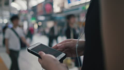 vidéos et rushes de japanese woman walking with smart phone in tokyo, japan - casque