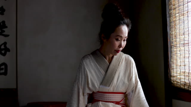 Japanese woman wearing Kimono by traditional window, Kyoto Japan