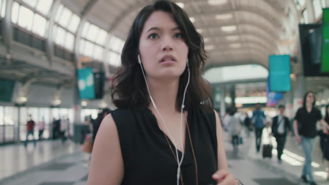 Japanese woman with headphones and smart phone walking, turning in train station in Tokyo, Japan