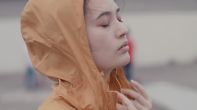 japanese woman with yellow headphones putting on hood of jacket in tokyo, japan. - anstrengung stock-videos und b-roll-filmmaterial