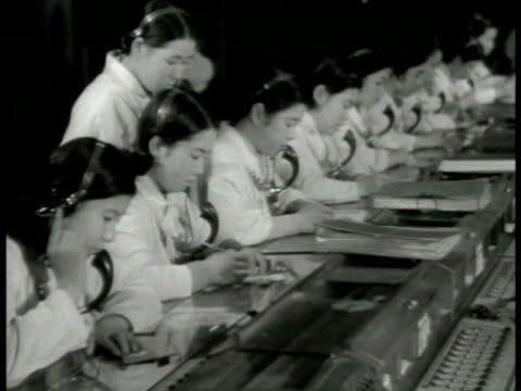 japanese women at telephone switchboard others in headsets w/ moving conveyor fg japanese male driving truck down ramp japanese workers on assembly... - 科学技術点の映像素材/bロール