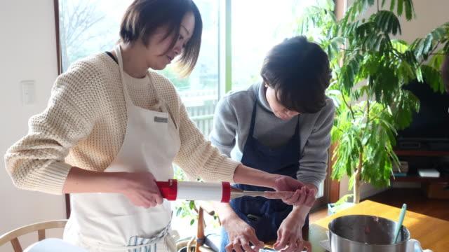 stockvideo's en b-roll-footage met japanse vrouwen die worst thuis koken - menselijke darmen