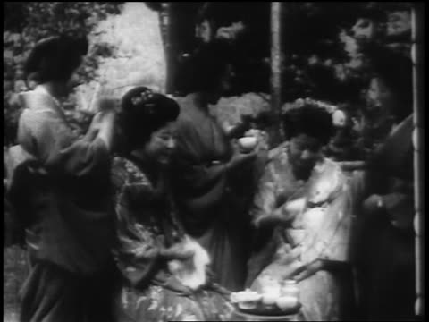 B/W 1898 Japanese women in traditional clothing laughing + drinking tea / one smoking / newsreel