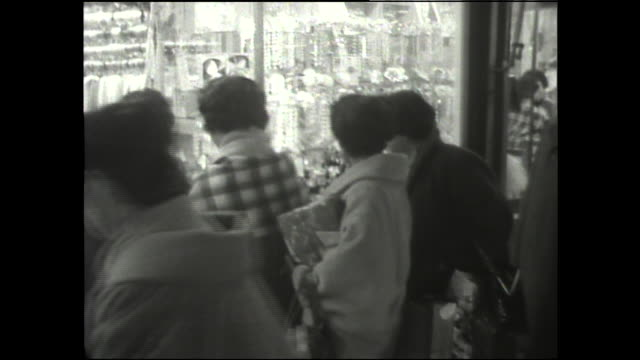 Japanese women peer in the window of a retail store during a year-end sale.
