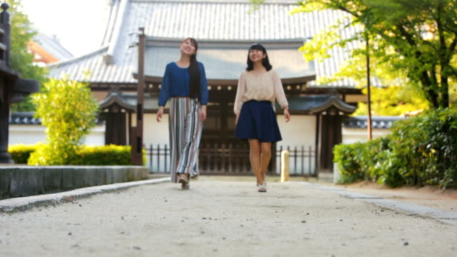 japanese women walking in the grounds of a buddhist temple - shrine stock videos & royalty-free footage