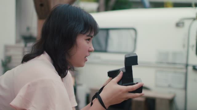 japanese women with instant camera talking to model in tokyo, japan - vignette stock videos & royalty-free footage