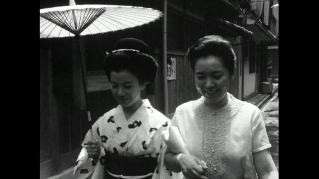 japanese women with umbrella walk along street; 1966 - traditional clothing stock videos & royalty-free footage