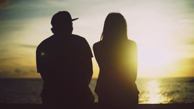 vidéos et rushes de japanese young couple sitting and talking at sunset. - casquette